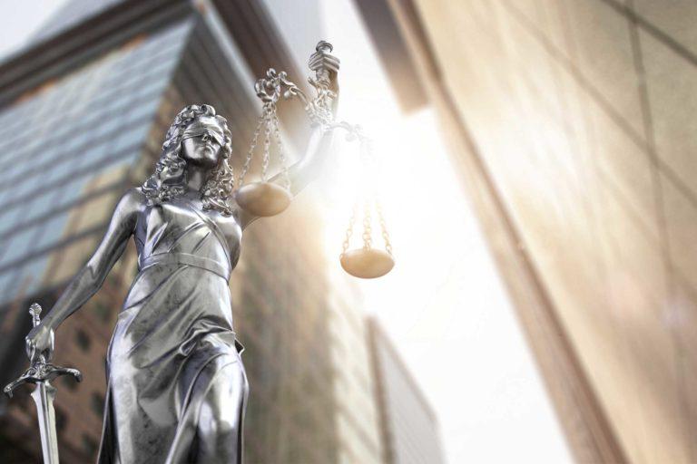 Statur steht vor einem Bankgebäude und hebt eine Waage in die Höhe